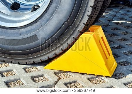 Yellow Chock At The Wheel Of A Parked Truck