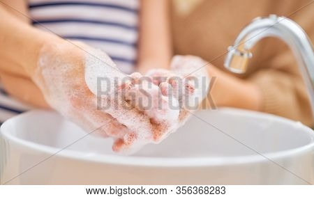 Kid and adult are washing their hands. Protection against infections and viruses. Close up.