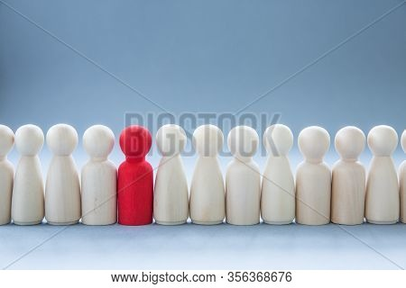 A Row Of Human Figures With A Single Individual Standing Out From The Rest Representing Individualit