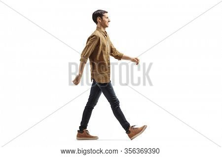 Full length profile shot of a casual young man in shirt and jeans walking with a smile isolated on white background