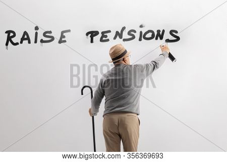 Pensioner writing graffiti on wall to raise pensions isolated on white background