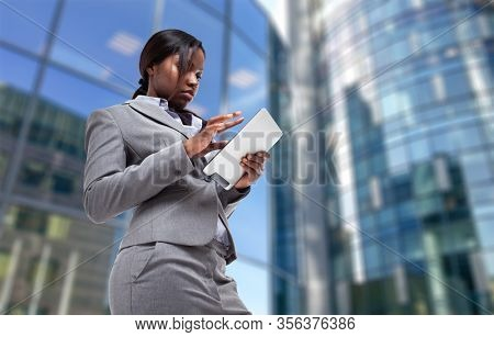 Young black business woman using a tablet in front of her office