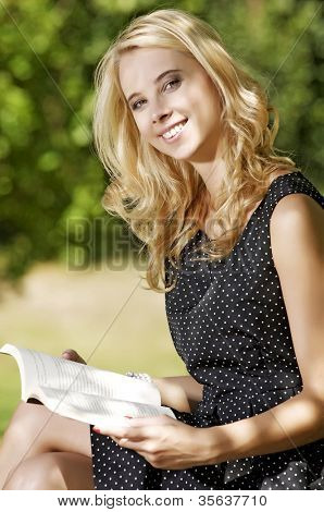 Young attracive blone woman reading book in park outdoor