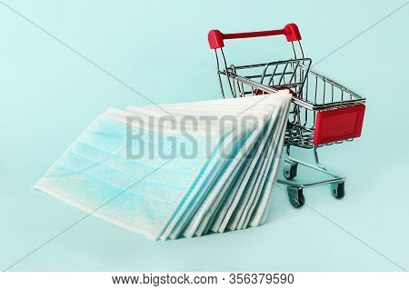 Several Of Medical Masks In The Shopping Cart.blue Colored Masks For Protection From Flu And Coronav