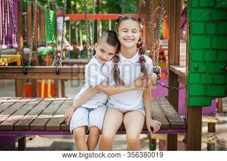 Cute Small Boy Hugging His Pretty Sister Sitting At The Playground. Concept Of Summer, Childhood And