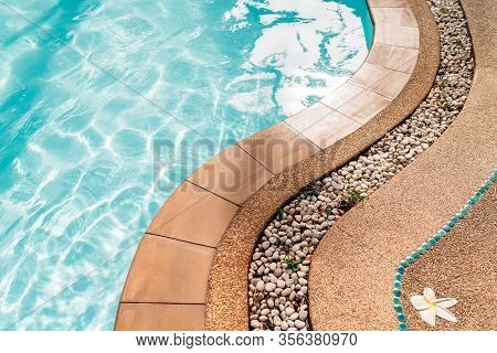 Curved Swimming Pool Paved Edge With Pebbles. Clean Transparent Pool Water Waves Background.