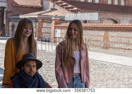 Sad Young Man In A Wheelchair With Some Young Girls Who Accompany Him