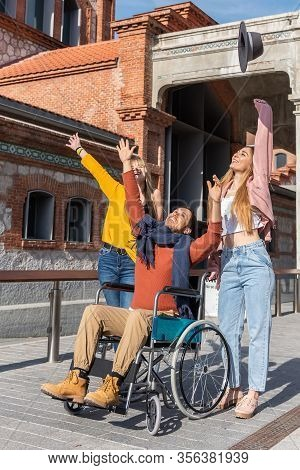 Young Man In A Wheelchair Tossing A Hat With Two Young Girls