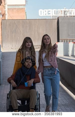 Young Man In A Wheelchair Next To Two Happy Young Girls Walking Down The Street
