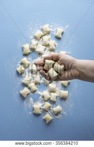 Raw Cheese Gnocchi Hold In Hand Over Blue Background. Uncooked Gnocchi Flat Lay. Italian Homemade Pa