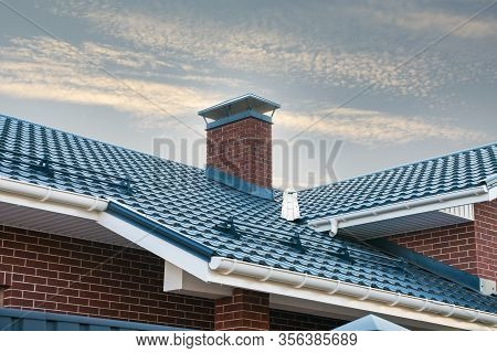 Newly Installed Construction Frame House Rain Gutter System On The Metal Roof Top. Brick Chimney Pip