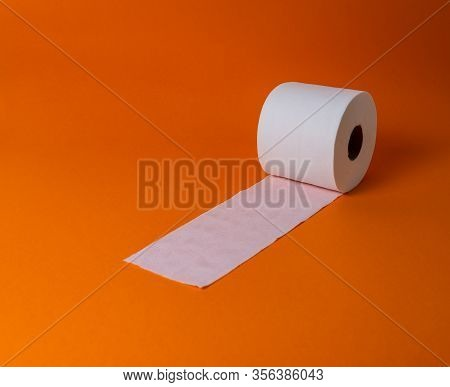 View Of A White Toilet Paper Roll Over An Orange Background And Copy Space