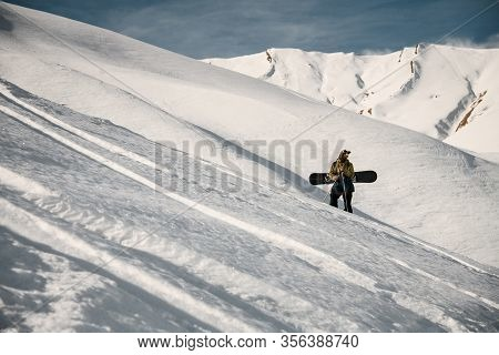Male Freerider With Snowboard Poses On Mountain Slope