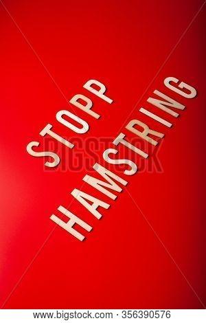 stopp hamstring norwegian word text wooden letter on red background coronavirus covid-19