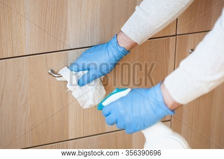 man hands in gloves disinfecting chest of drawers handle, killing virus on surface