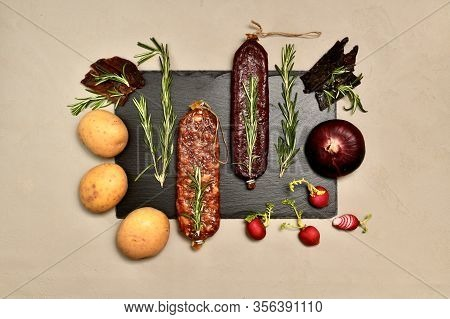 Raw Smoked Cured Meats With Rosemary And Vegetables On A Black Slate Substrate With The Center On A