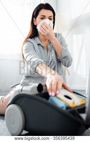 Selective Focus Of Allergic Woman Covering Mouth With Tissue And Reaching For Dust Bag In Vacuum Cle