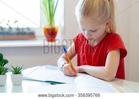 Serios Blonde Schoolgirl Sitting At Home And Doing School Homework, Writing In Notebook. Training Bo