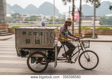 Guilin, China - May 11, 2010: Downtown. Man With Straw Hat And Orange Security Vest Rides Pedal Tric