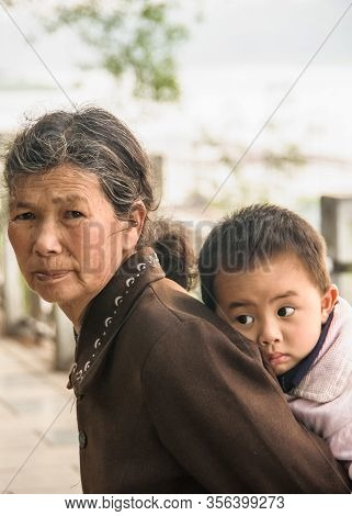 Guilin, China - May 11, 2010: Downtown. Closeup Of Grandmother In Brown Garb Carrying Young Boy On H
