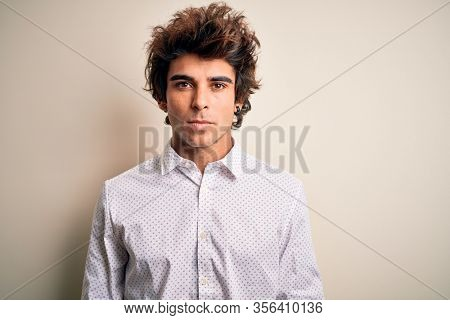 Young handsome businessman wearing elegant shirt standing over isolated white background with serious expression on face. Simple and natural looking at the camera.