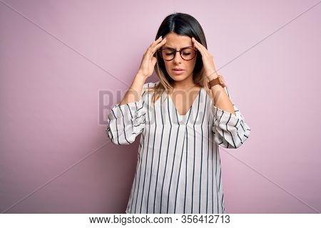 Young beautiful woman wearing casual striped t-shirt and glasses over pink background with hand on headache because stress. Suffering migraine.