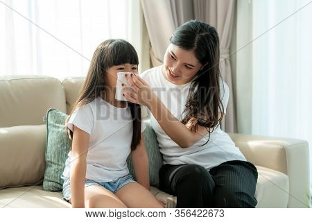 Portrait Of Cut Asian Girl Blowing Snot Into The Napkin With Her Mother Is Keeping It Near Her Nose