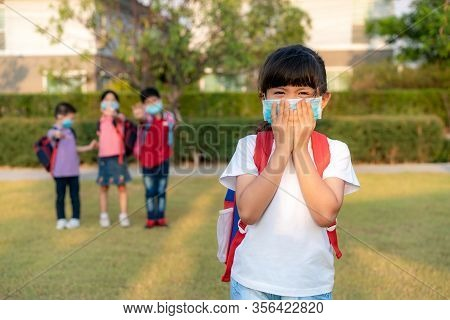 Asian Girl Preschool Child Student Wearing Healthy Face Mask Sneeze With Friends In Background. The