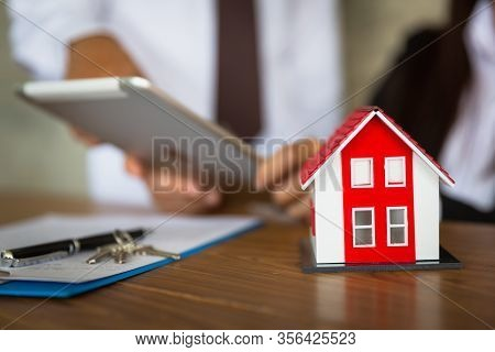 Businessmen And Customers Are Signing Home Purchase Agreements. Hand Holding The Pen Signing Purchas