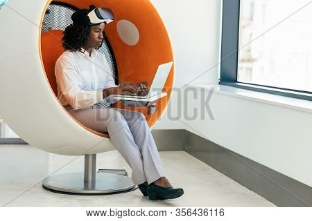 Businesswoman Using Computer In Vr Studio. Black Woman In Office Clothes And Virtual Reality Goggles