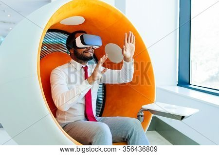 Happy Amazed Office Employee Enjoying Vr Experience. Man Wearing Vr Glasses, Sitting In Interactive