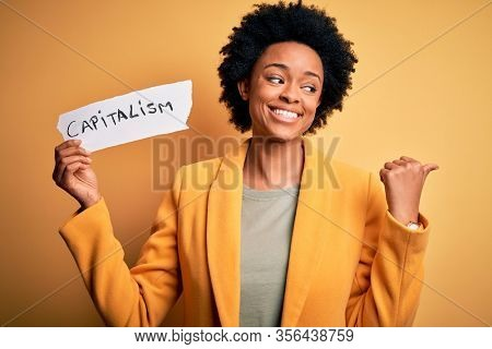 African American afro businesswoman with curly hair holding paper with capitalism message pointing and showing with thumb up to the side with happy face smiling