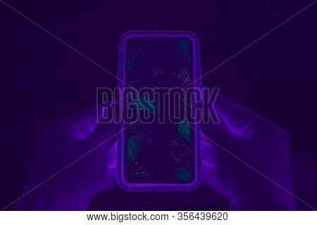 Hands Holding Cell Phone With Dirty Contaminated Touch Screen - Uv Blacklight Exposing Infectious Ba
