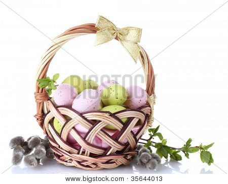 basket with Easter eggs and pussy-willow twigs isolated on white