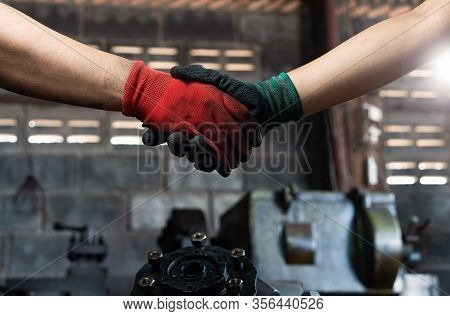 Male And Female Industrial Workers Shaking Hands In Factory Workshop Wearing Protective Workwear - B