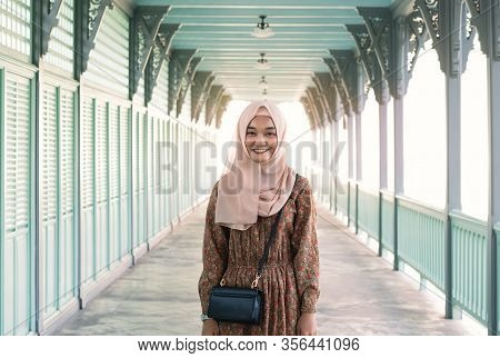 Young And Happy Asian Muslim Girl Standing Outdoors With Bright Afternoon Sunshine Behind Her - Smil