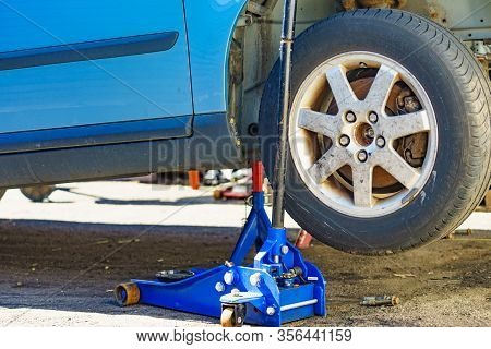 Bergen, Norway - June 30, 2018: Blue Hydraulic Jack To Lift Car In Use. Michelin Logo On Tire.