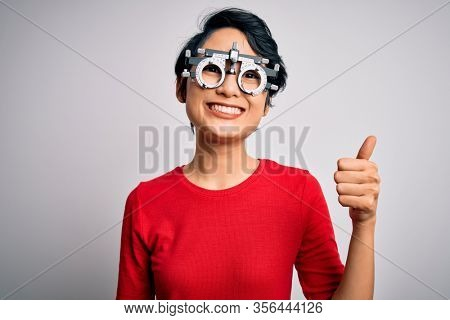 Young beautiful asian girl wearing optometry glasses standing over isolated white background doing happy thumbs up gesture with hand. Approving expression looking at the camera showing success.