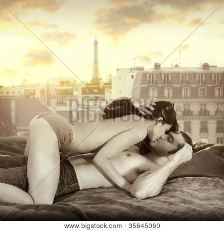 Young sexy couple making passionate love in bed against window overlooking Paris skyline with retro vintage sepia tones