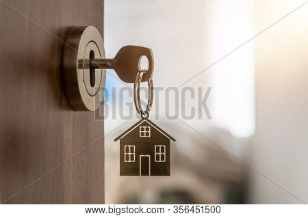 Open Door To A New Home With Key And Home Shaped Keychain. Mortgage, Investment, Real Estate, Proper
