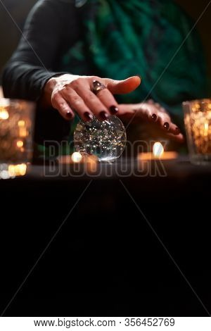 Fortuneteller female divining on magic ball at table with burning candles