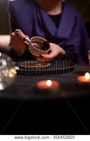Close-up of female fortuneteller's hands divining on coffee grounds at table with predictive ball