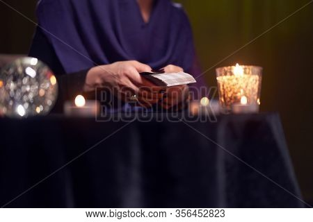Fortuneteller divines on cards sitting at table with burning candles, magic ball