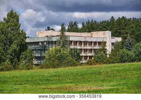 Abandoned Concrete Building Surrounded By Trees. Landscape With An Abandoned Building.