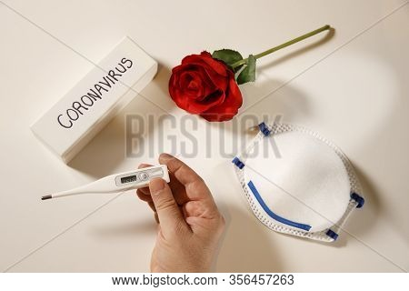 Caronavirus Concept, Hand Holding Temperature Thermometer With Personal Mask And Red Rose On White F