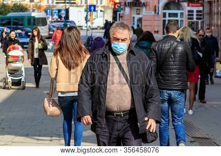 Uzhgorod, Ukraine - March 18, 2020: A Man In A Medical Mask Walks In The City Center During Quaranti