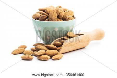 Dried almonds nuts in bowl and wooden scoop isolated on white background.