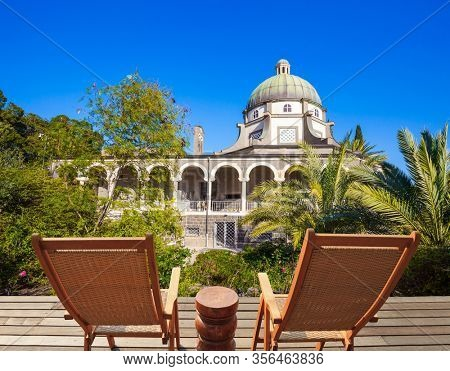 Catholic Church of the Beatitudes and park around the monastery. Two comfortable wooden chairs - deck chairs on the platform for relaxing. The concept of religious pilgrimage and photo tourism