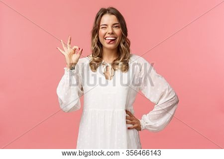 Portrait Of Happy Smiling Blond Woman With Short Curly Haircut, Show Tongue And Okay Sign, Say Alrig