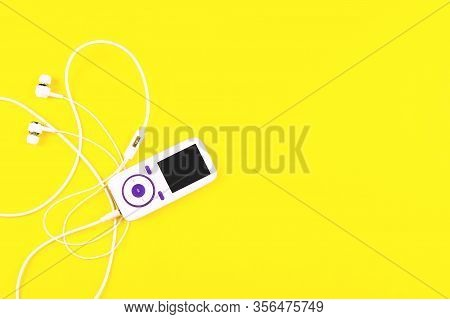 White Music Player With Earphones On Yellow Background. Place For Text, Flat Lay.